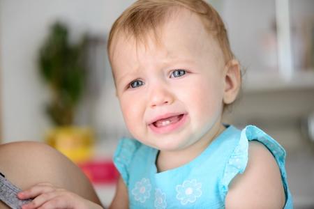 小さな赤ちゃんが泣いているハードです。彼女のほおを涙が流れ 写真素材