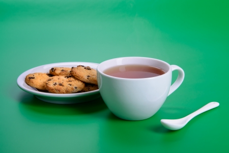 white cup of hot tea and cookies on green background photo