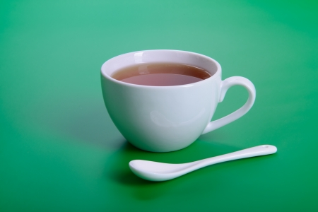 white cup of hot tea with spoon on green background photo