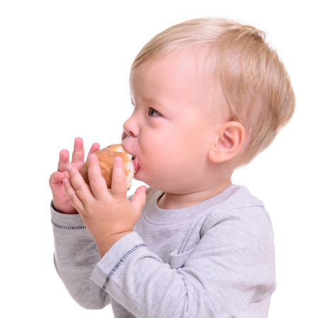 portrait of cute little caucasian baby sits and eats bread. isolated on white background. baby 1 year photo