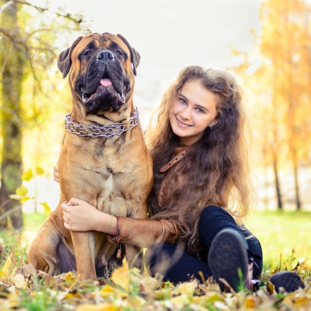 teen girl and dog bullmastiff sit in the park in autumn Stock Photo