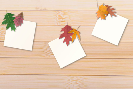 autumn leaves with paper sheet on wooden background texture photo