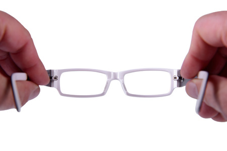 Reading eyeglasses in hand isolated on white photo