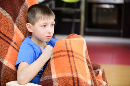 sick child: Little boy sitting covered with a blanket at home