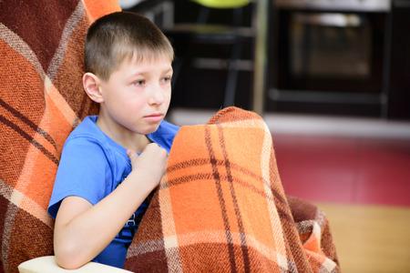 enfant malade: Petit gar�on assis recouvert d'une couverture � la maison