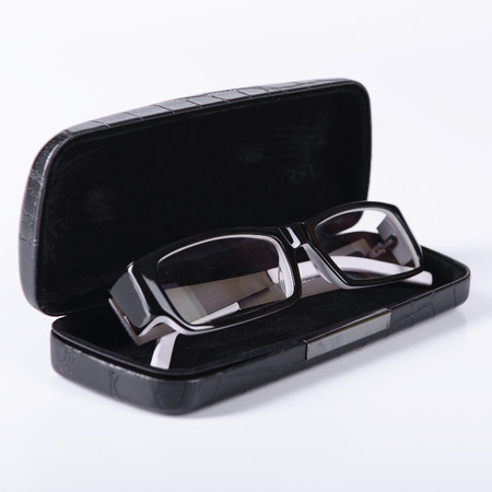 optical glasses on a light gray background in a case photo