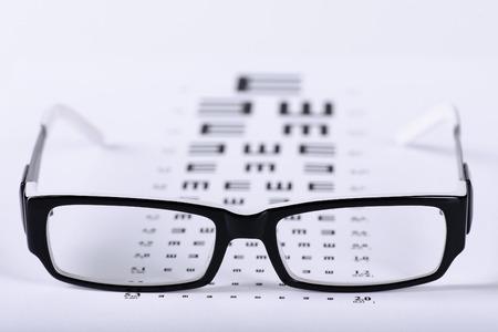 oči: Čtení černé brýle a oční graf zblízka na světlém pozadí Reklamní fotografie