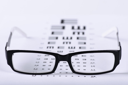eye closeup: Reading black eyeglasses and eye chart close-up on a light background