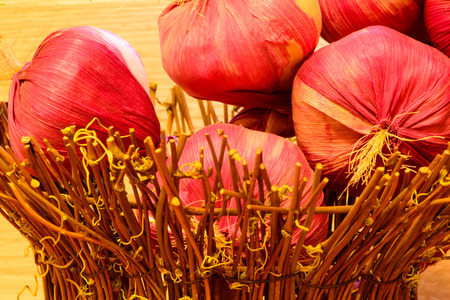 close up of onions in a basket: ripe vegetable harvest onions in wooden basket