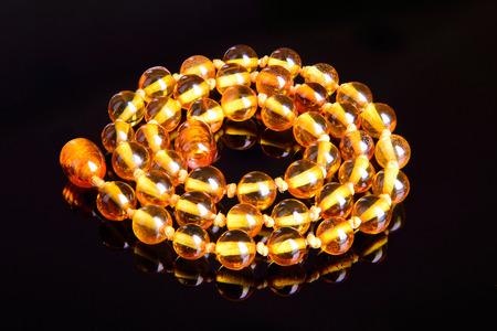 Amber beads round fashion accessory decoration on black background