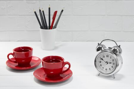 comfortable workplace office - work table with two red coffee or tea mugs - home office - office or school lunch - light background with brick wall