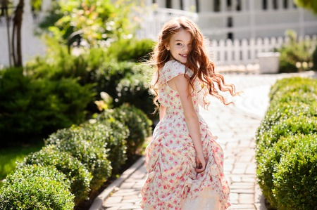 Charming redhead girl. She poses and smiles in the outdoors.