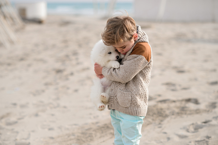 The child on seacoast plays with the puppy Stock Photo