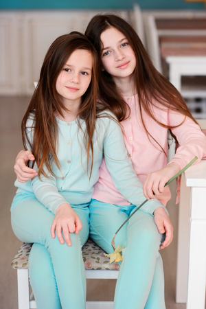 Beautiful girls at dawn indoors. Children with flowers. Stock Photo