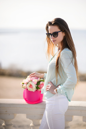 Beautiful girl with flowers in hands outdoors. Spring sunny day.