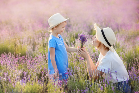Mom and girl walk on the lavender field.