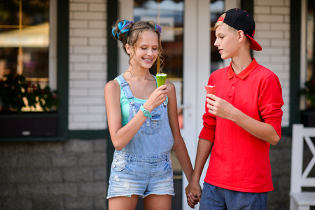 Young couple eating ice cream. Attractive friends at cafe.