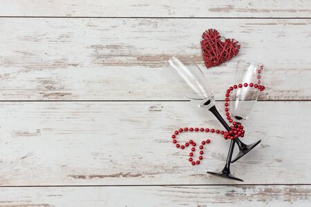 Valentines day romantic background - red heart, glasses with bead chain. Holiday dinner concept. Top view. Copy space.