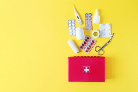 First aid kit red box with medical equipment and medications for emergency top view on pastel yellow background. Copy space.