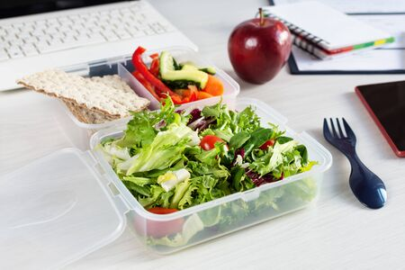 Vegetables and fresh green salad in lunch box on working desk with laptop and other office supplies. Healthy business lunch at workplace.