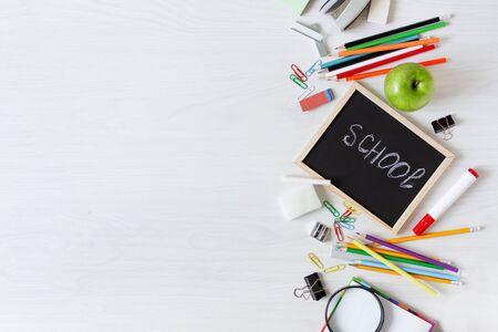 Schulbedarf auf weißer Holztisch-Draufsicht. Schreibwaren. Zurück zum Schulkonzept. Standard-Bild