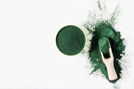 Organic green spirulina powder top view on white background. Super foods, food supplement source of vitamin protein and beta carotene.