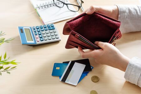 Woman hands with empty wallet, a few coins and credit cards on the table with calculator. Unemployment and dismissal concept. Money crisis. 版權商用圖片