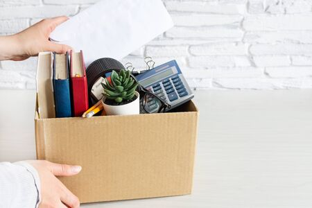 Business woman packing personal company belongings into cardboard box. Dismissal or resignation concept. Company bankruptcy and economy crisis.