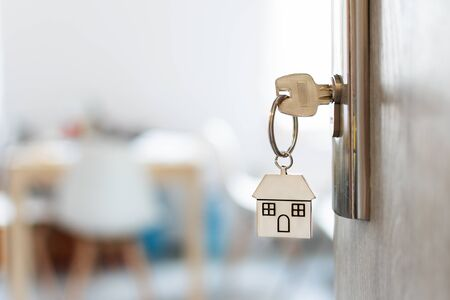 Key with keychain in a house shape in the door keyhole. Buy new home concept. Real estate market. Banque d'images