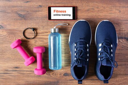 Fitness equipment, sport shoes and smartphone on wooden background top view. App for sport training indoors. Online Fitness training concept. Online workout staying at home.