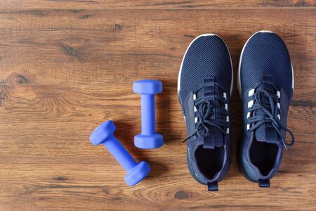 Sport shoes and dumbbells on wooden background top view. Fitness training concept. Copy space.