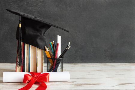 Academic cap and graduation diploma scroll and tied with red ribbon on white wooden table over black chalkboard.