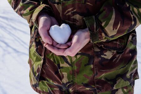 Soldier is taking snow heart in his hands. Courage and love of soldier. Snow cold heart.
