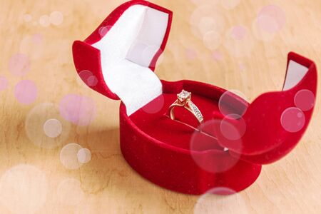 Engagement ring in a gift box on wooden background. Marriage proposal concept. 스톡 콘텐츠