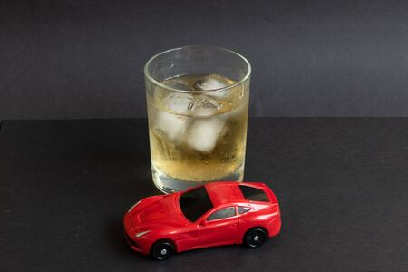Alcohol and car toy on color background. Driving in a drunken state concept. 免版税图像