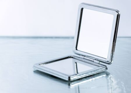 Small pocket mirror on glass table background. Elegance female accessory.