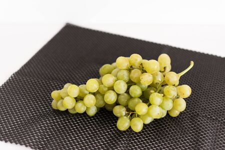 Bunch of green grapes on white wooden background. Minimalism concet. Copy space.