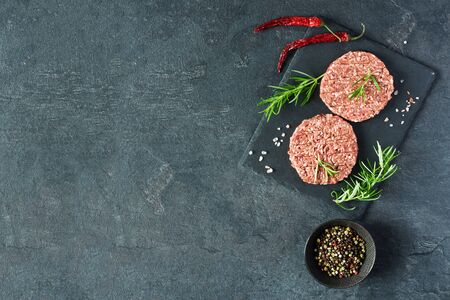 Raw burger cutlets made from minced fresh meat with rosematy and chili on a slate board top view. Ingredients for making burgers. Copy space.