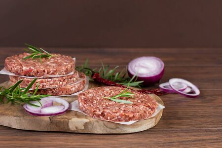 Raw burger cutlets made from minced fresh meet with spices and herbs on wooden background. Ingredients for making burgers.