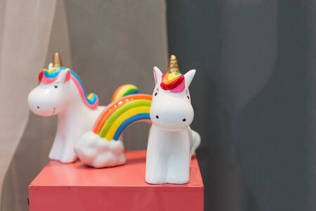 Ceramic souvenir unicorn toy money box with colorful rainbow on pink table.