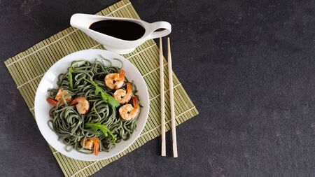 Soba spirulina noodles with shrimps on a white plate top view. Asian food creative concept.
