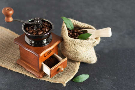 Manual vintage coffee grinder and coffee beans in a burlap bag on a wooden table. Copy space.