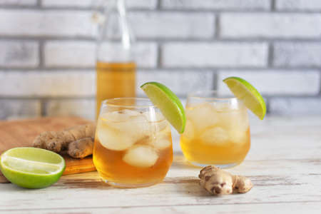 Fresh Ginger Ale with lime and ice or Kombucha in Bottle - Homemade lemon and ginger organic probiotic drink, copy space.