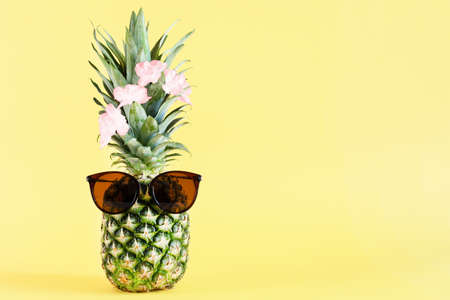 Funny pineapple with sunglasses on yellow pastel background. Summer background. Copy space.