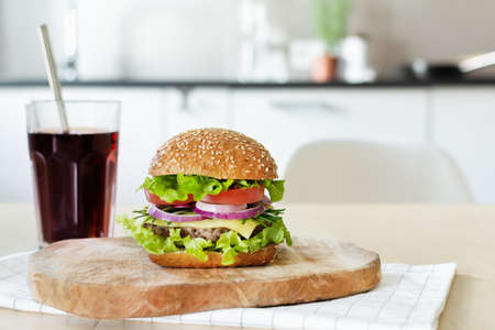 Beef burger with fresh salad, cheese and tomatoes on cutting board on the table in the bright kitchen. A glass of refreshment cola drink. Fast food, unhealthy eating.