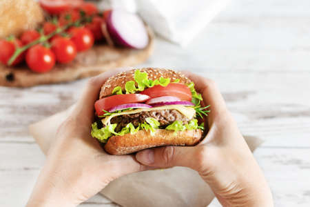 Woman hands hold beef burger with fresh salad, cheese and tomatoes over table. Fast food, unhealthy eating.