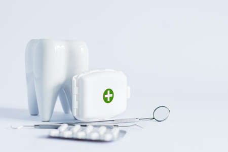 Model of white tooth, medical pills and dentistry tools on white background. Teeth treatment concept.