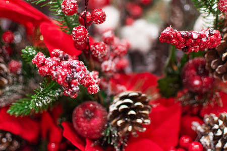 Fake plant of pine needles, pine cone and red berries for Christmas home decoration.