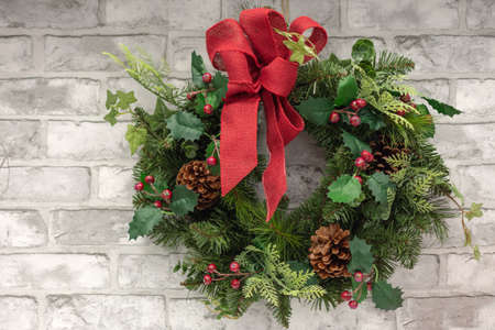 Christmas decoration wreath with red holly berries, fir cones and red ribbon bow on grey brick wall background.