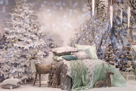 Cozy bedroom interior decorated with Christmas details: fluffy deer, Christmas tree, branches at the wall near bed with snow. Home with Christmas decorations in blue colors.